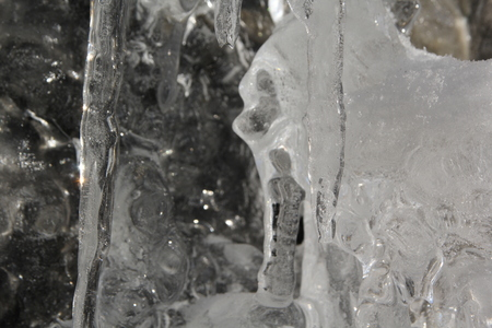 Icicles hanging on a ledge with rocky bacground after thawing