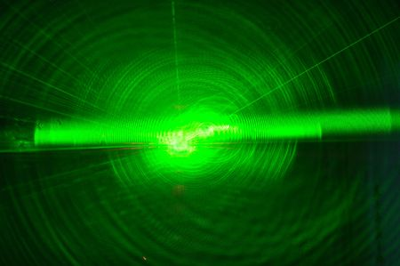 Bright green laser beam from darkness Stock Photo