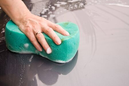 The female hand washes with sponge the car