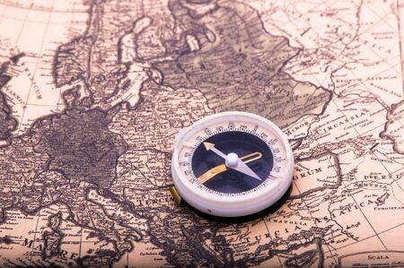compass lies on an ancient world map photo