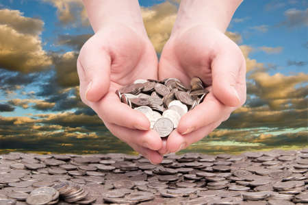 womans hands holding a handful of coins photo