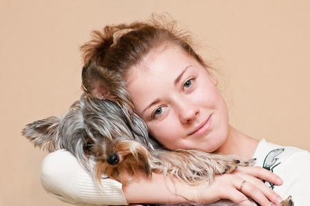 The girl holds a dog of a small terrier on hands photo