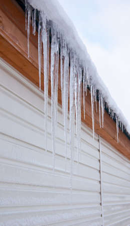 long icicles hanging from the roof of the house Stock Photo - 8556082