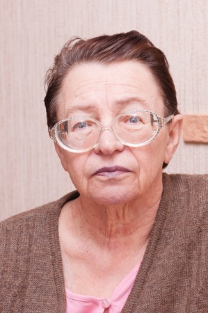 old woman with glasses looking thoughtfully photo
