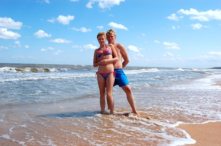 young man and a girl on the beach photo