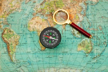 compass and magnifying glass lie on the topographic map Stock Photo