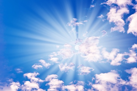 sun with clouds against the blue sky