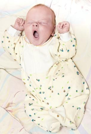 生まれたばかりの赤ちゃんを毛布で横になっています。