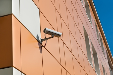 video surveillance camera hanging on the wall of a building Stock Photo - 13529199