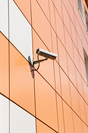 video surveillance camera hanging on the wall of a building photo