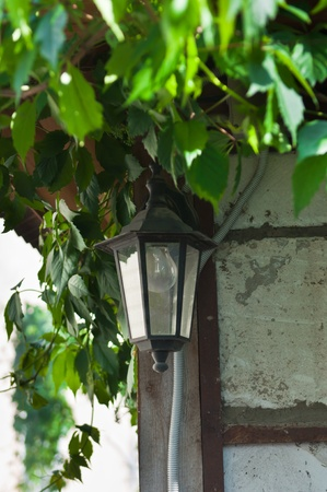 Old lantern hanging on the wall photo