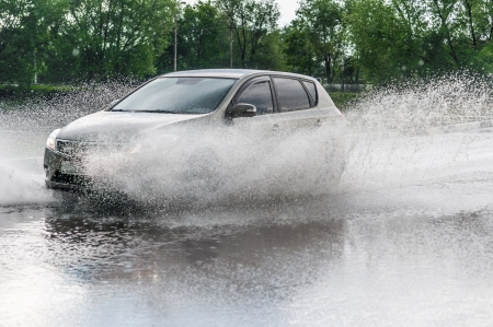 Car rides on big water in the rain