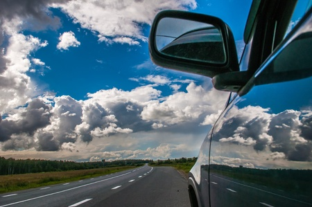 part of the car against the sky with a cloud