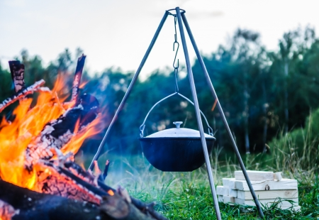 kettle on a tripod hanging around a bonfire