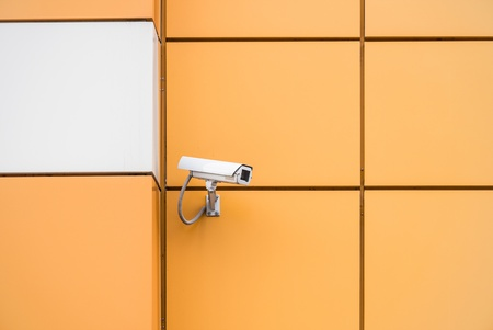 video surveillance camera hanging on the wall of a building Stock Photo - 16677506