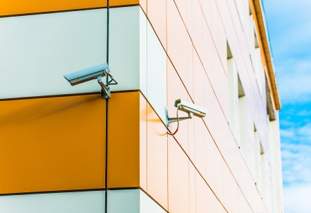 video surveillance camera hanging on the wall of a building Stock Photo - 16677593
