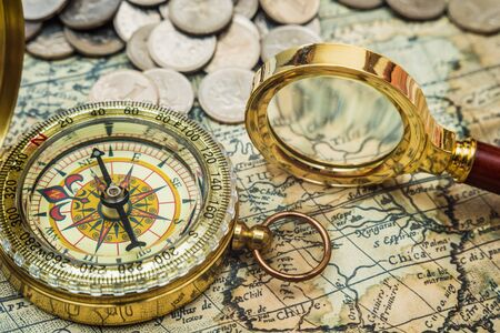 compass and magnifying glass gold color on the old map with coins photo