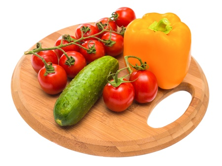 cucumber pepper and tomatoes on a cutting board photo