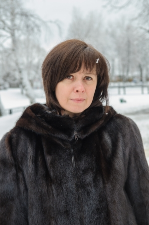 middle-aged woman in a mink coat against winter photo