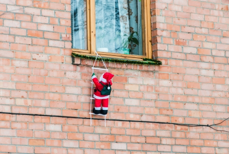 Santa Claus climbing out of the window on the stairs Stock Photo