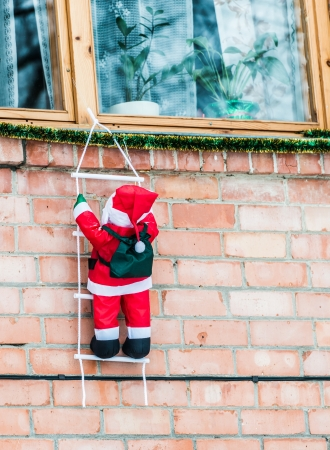Santa Claus climbing out of the window on the stairs photo