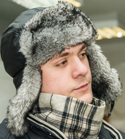young man in winter fur hat with ear flaps photo