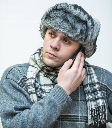 a young man with a phone in a winter cap photo
