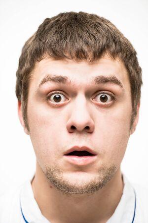 gestos de la cara: Un hombre joven hace un cara a cara Foto de archivo