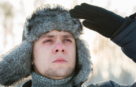 a man in a fur winter hat with ear flaps photo