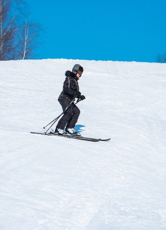middle-aged woman alpine skiing in the snow in winter photo