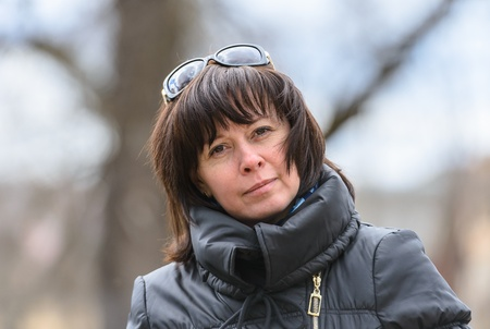 portrait of a middle-aged brunette woman in a black jacket outdoors photo