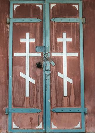 double cross: doppia porta d'acciaio con un marrone attraversare l'ingresso della chiesa Archivio Fotografico