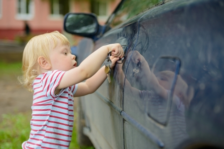 little kid wants to open a car door key photo