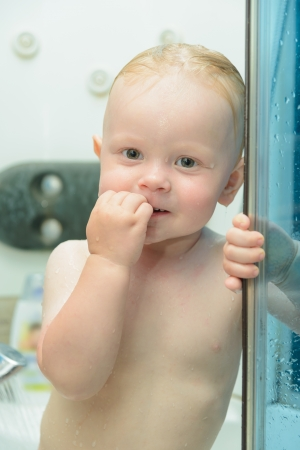 small red-haired boy is bathed in the shower photo