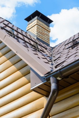 青い空を背景に、家の屋根の上の煙突