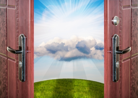 open door with a view of green meadow illuminated by bright sunshine Stockfoto