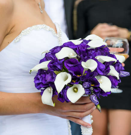 bride in a white dress holding a wedding bouquet of flowers photo