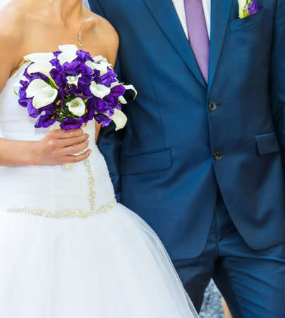 the groom in a blue suit and a bride holding a wedding bouquet of flowers photo