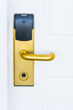 white door with an electronic lock and handle of gold color photo