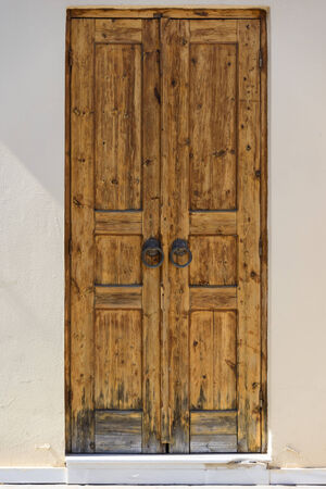 old wooden door in the wall of the building photo