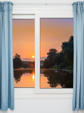 view from the window with the curtains of the sunset over the water photo