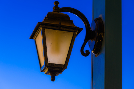 source of iron: vintage lamp on a pole in the evening after sunset