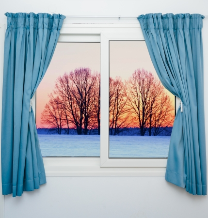 view from the window with the curtains of the sunset over the snow Foto de archivo
