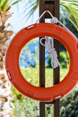 hanging around: naranja salvavidas con una cuerda que cuelga alrededor de la piscina