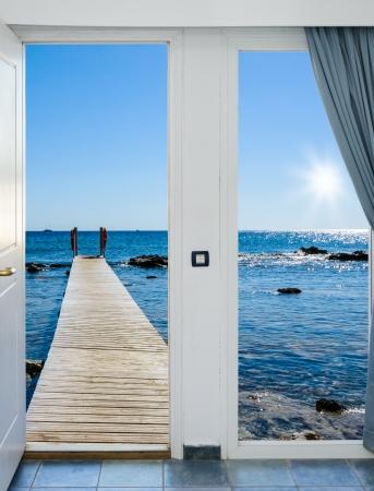 vis�o: a vista da janela aberta sobre o mar, com um cais