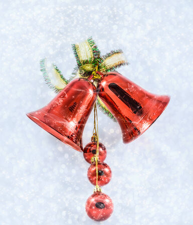 red Christmas bells with bow on shiny snowflakes photo