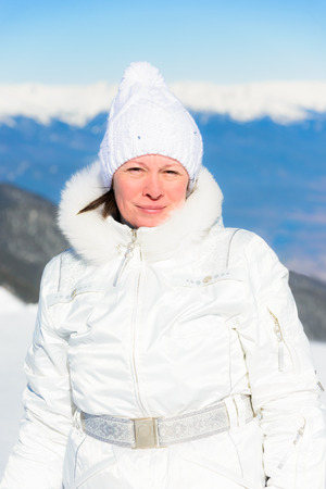 Middle-aged woman in a knitted hat and white sports jacket.  Tourism fresh air on snowy peaks of mountains and blue sky ski resort.  Portrait of a winter sunny day photo