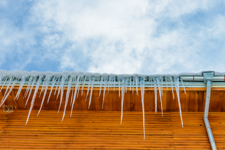 edge of the roof house with icicles on blue sky background photo