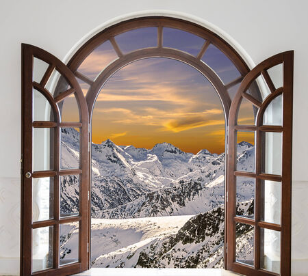 Arch door opened with views of the peaks of snowy mountains and sunset in the cloud