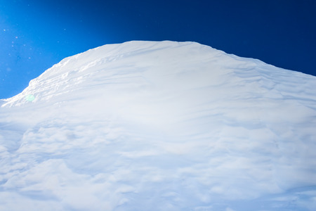 hummock: big snow hummock of pure white snow on a background of blue sky